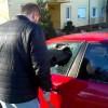 A man breaks his own car's window after locking keys